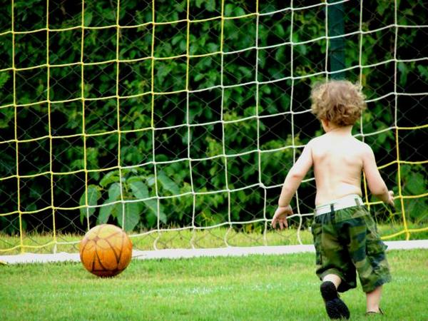 crianca-jogar-futebol-cuidados-coluna